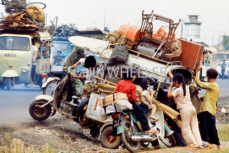 Vietnamese refugees fleeing advancing North Vietnamese army try to right their overloaded scooter on Highway One near Saigon during the last days of the Vietnam War