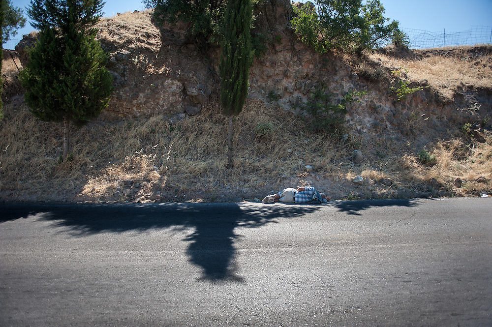 ASyrian refugee sleeping by the road. The man later told us that he was so tired from walking that he couldn't look for a better shelter. Refugees land at the northern shores of the island of Lesbos and then they have to walk the 9 hour distance to one of the camps.