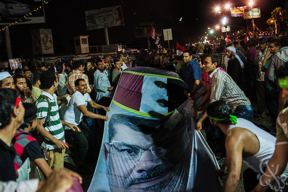 Anti-Coup protesters wave a long banner with photos of deposed Egyptian president Mohamed Morsi while taking part in Friday July 19, 2013 demonstrations at the Rabaa al-Adawiya mosque in Nasr City. For 3 weeks, protesters angry with the decision of the military to remove Morsi from power have been camped out at the mosque by the thousands, and have vowed to remain until Morsi is returned to power.