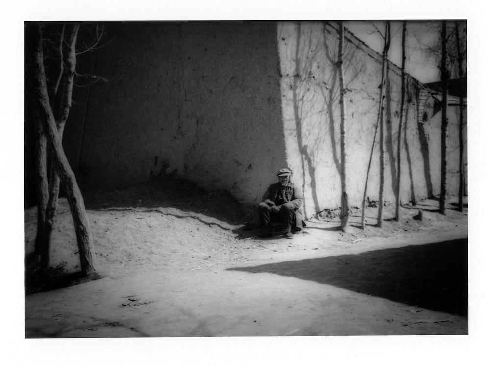Hui Muslim man resting in the winter sun.  Ganxu Province, China.  1996