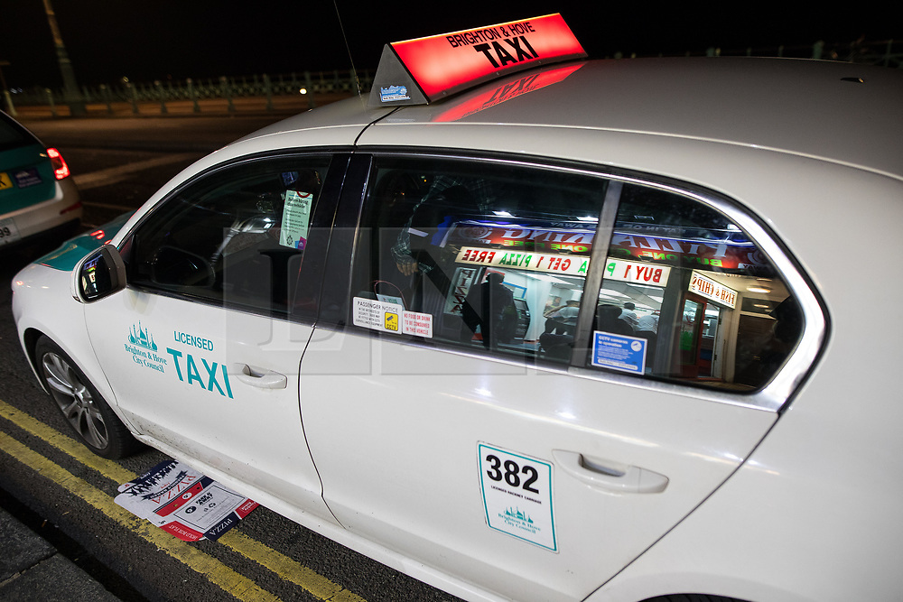 © Licensed to London News Pictures . 26/09/2017. Brighton, UK. The lights of a pizza takeaway restaurant reflected in a minicab window . Revellers at the end of a night out in Brighton during Freshers week , when university students traditionally enjoy the bars and clubs during their first nights out in a new city . Photo credit: Joel Goodman/LNP