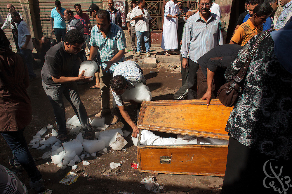 Egyptians try to keep the bodies of their dead relatives iced and perfumed as they wait outdoors for autopsies and death certificates to be issued August 15, 2014 at the Zeinhoum morgue in Cairo, Egypt.  A day after a violent raid by security forces on the supporters of deposed Egyptian President Mohamed Morsi, the country is trying to come to terms with the news that at least 600 people were killed and thousands more injured across Egypt during the raid on Rabaah al-Adawiya, and another, smaller protest camp in the district of Giza across town.
