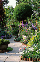curved stone path through well planted garden