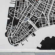 A woman crossing in front of a map of Manhattan.