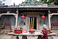 Woman Lighting incense at Tin Hau Temple, Hong Kong