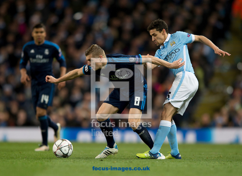 Toni Kroos of Real Madrid (centre) holds off Jesus Navas of Manchester City during the UEFA Champions League match at the Etihad Stadium, Manchester<br /> Picture by Russell Hart/Focus Images Ltd 07791 688 420<br /> 26/04/2016