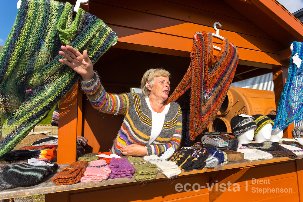 A local Icelandic woman sells colourful local handicraft Icelandic woollen gloves, hats, and shawls, at a road-side stand. Siglufjordur, Iceland. July.