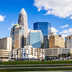Charlotte skyline panorama at Romare Bearden Park with downtown Charlotte city buildings against a blue sky with clouds. Includes One Wells Fargo Center, Two Wells Fargo Center, Bank of America Corporate Center, Bank of America Plaza, 121 West Trade building, and Carillon Tower. Charlotte, North Carolina is a major city in the Eastern United States of America