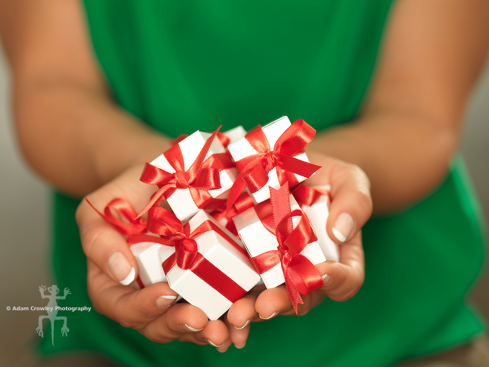 Close up of a woman's hands holding several small white gift boxes wrapped with red ribbons.