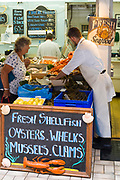 Customer shopping at popular Dunn-Ross Fisheries fish stall at Beresford Street Market, St Helier, Jersey, Channel Isles