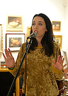 Huntington, New York, USA. February 20, 2014. A young woman singer performs at the Jingle Boom Holiday Bash, at the Main Street Gallery of Huntington Arts Council. Sparkboom, an HAC project, provides events such as this geared to Gen-Y, 18-34 years of age, to address the 'brain drain' of creative young professionals of Long Island. The paintings on the art gallery walls were the Annual Juried Still Life Show.