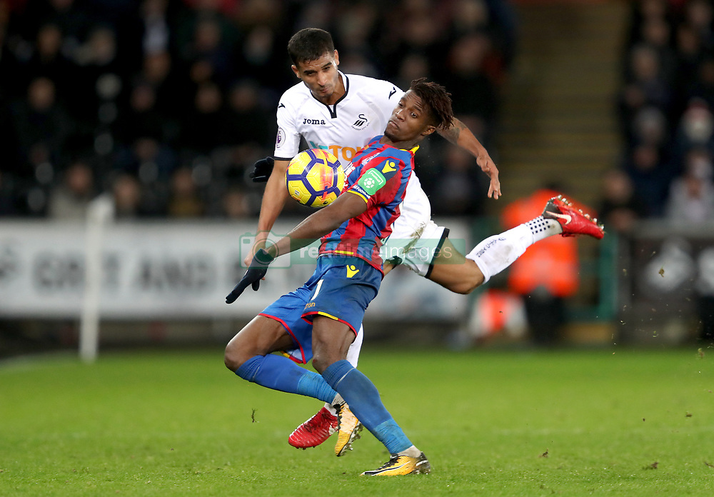 Swansea City's Kyle Naughton and Crystal Palace's Wilfried Zaha (front) battle for the ball during the Premier League match at the Liberty Stadium, Swansea.