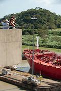 Tourists watching a cargo ship transit at Miraflores locks Visitors Center. Panama Canal, Panama City, Panama, Central America.