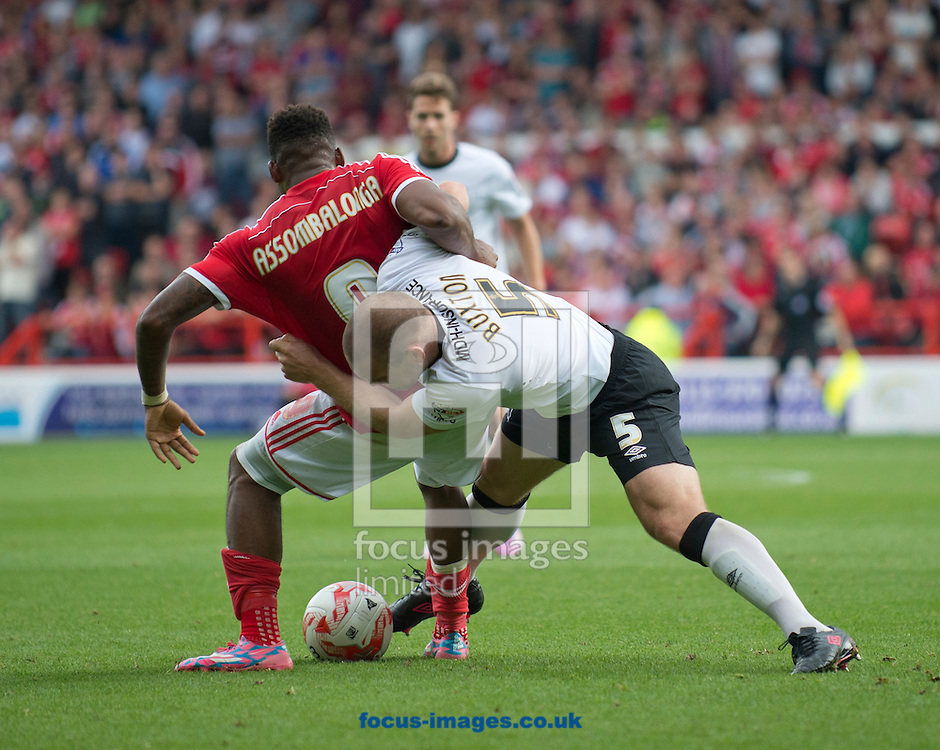 Jake Buxton of Derby County wrestles Britt Assombalonga of Nottingham Forest to the ground during the Sky Bet Championship match at the City Ground, Nottingham<br /> Picture by Russell Hart/Focus Images Ltd 07791 688 420<br /> 14/09/2014