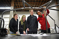 Mechanical engineering's Bryon Spells (right) points out recent welding work to SolarPack teammates while checking on the progress of their car at Eastern Rod and Customs.