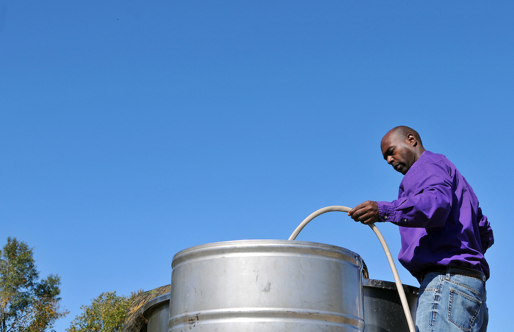 Dr. Cedric Sims, agronomy specialist in the Alcorn State University Extension Program, moves sugarcane sugar juice into a vat during a sugarcane syrup making demonstration on Dennis Dahmer's property off of Monroe Road Wednesday. Bryant Hawkins/ Hattiesburg American