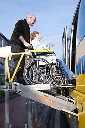 Bus driver helping wheelchair user onto coach using a special ramp,