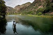 Donovan Talbott of Palisade, Co. fly fishes near the East Portal just outside the boundaries of the Black Canyon of the Gunnison National Park. The park's unique and spectacular landscape was formed slowly over thousands of years by the action of water and rock scouring down through the  rock walls of the canyon. Talbott, a peach farmer, had just finished up harvesting for the year and said it was his first time fishing on this stretch of the Gunnison River. No other canyon in North America combines the narrow opening, sheer walls, and startling depths offered by the Black Canyon of the Gunnison. The same water that formed the canyon is also necessary for its future. The plants and animals in the canyon rely on a steady flow year round as well as occasional peak flows to maintain the ecosystem in the canyon. The Bureau of Reclamation has a number of dams upstream and Gale Norton, The Secretary of the Interior, worked out a deal with everyone involved but environmentalists disagreed with it and the issue is tied up in the courts. Black Canyon of the Gunnison National Park is a United States National Park located in western Colorado, and managed by the National Park Service. The park contains 12 miles of the 48 mile long canyon of the Gunnison river. The national park itself contains the deepest and most dramatic section of the canyon, but the canyon continues upstream into the Curecanti National Recreation Area and downstream into the Gunnison Gorge National Conservation Area. The Gunnison River drops an average of 43 feet per mile (8 m/km) through the entire canyon, making it one of the steepest mountain descents in North America. The Black Canyon is so named on account of its steepness which makes it difficult for sunlight to penetrate very far down the canyon. As a result, the canyon walls are most often in shadow, causing the rocky walls to appear black. At its narrowest point the canyon is only 40 feet (12 meters) across at the river. The extreme steepness and d