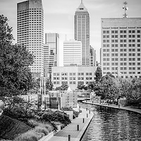 Indianapolis skyline black and white photo with Canal Walk and downtown Indianapolis city buildings. The Indiana Central Canal was built in the 1800s and Canal Walk serves as a recreational attraction.