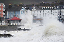 © London News Pictures. 29/11/2015. Storm force winds and high tides bring huge waves crashing into the sea defences in Aberystwyth on the west Wales coast. A yellow 'be aware' warning has been issued by the Met Office for the whole of Wales over the weekend. Gusts around the western coasts could reach 70mph, bringing the possibility of property damage and travel disruption Photo credit: Keith Morris/LNP