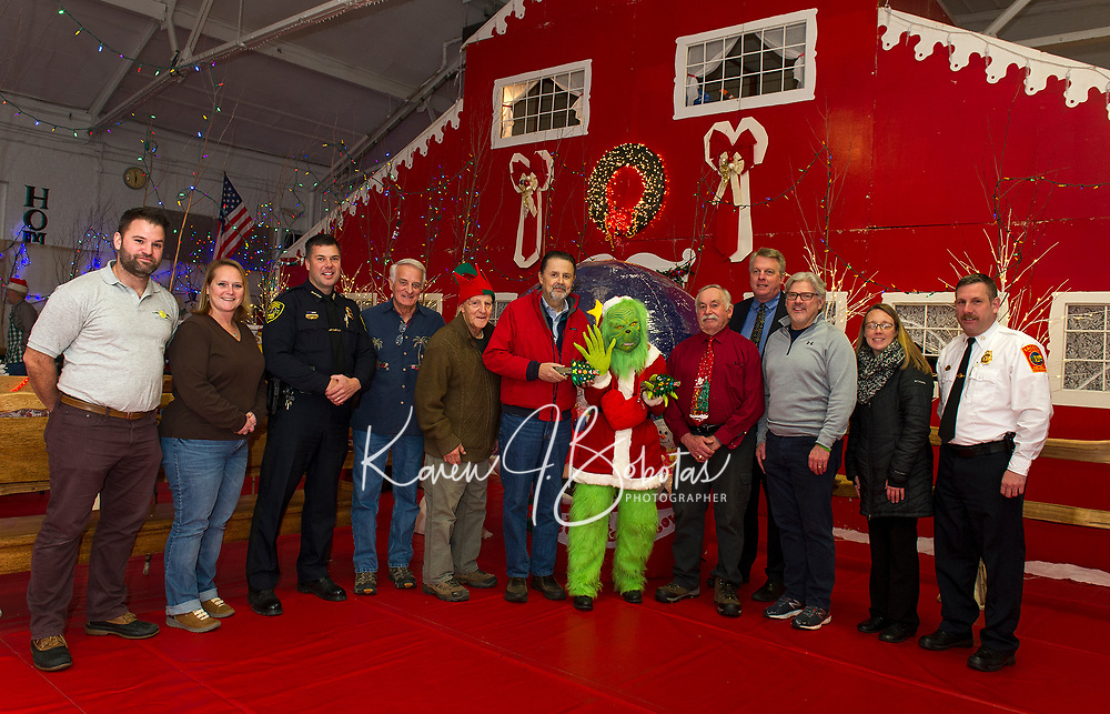 "Mayor Grinch is honored and presented the key to Christmas Village on opening night Thursday evening. l-r  Matt Mansur, Amy Lovisek Laconia Parks and Recreation, Police Chief Matt Canfield, Councilor Bob Hamel, ""Tinsel"" Ernie Bolduc, Mayor Ed Engler, Mayor Grinch, Councilor Mark Haynes, City Manager Scott Myers, Mayor-elect Andrew Hosmer, Laconia Schoolboard Heather Lounsbury and Fire Chief Kirk Beattie. (Karen Bobotas/for the Laconia Daily Sun)"