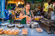 19 OCTOBER 2012 - BANGKOK, THAILAND:   A waffle vendor and her cart in the Bangkok Flower Market. The Bangkok Flower Market (Pak Klong Talad) is the biggest wholesale and retail fresh flower market in Bangkok.  The market is busiest between 3:30AM and 6AM. Thais grow and use a lot of flowers. Some, like marigolds and lotus, are used for religious purposes. Others are purely ornamental.         PHOTO BY JACK KURTZ