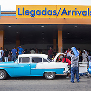 An American Airlines flight from Miami with mostly Cuban Americans arrives at Jose Marti airport in Havana carrying bulging suitcases and duffle bags with goods from the United States. Old classic cars wait to take the arriving passengers outside the arrivals terminal. <br />