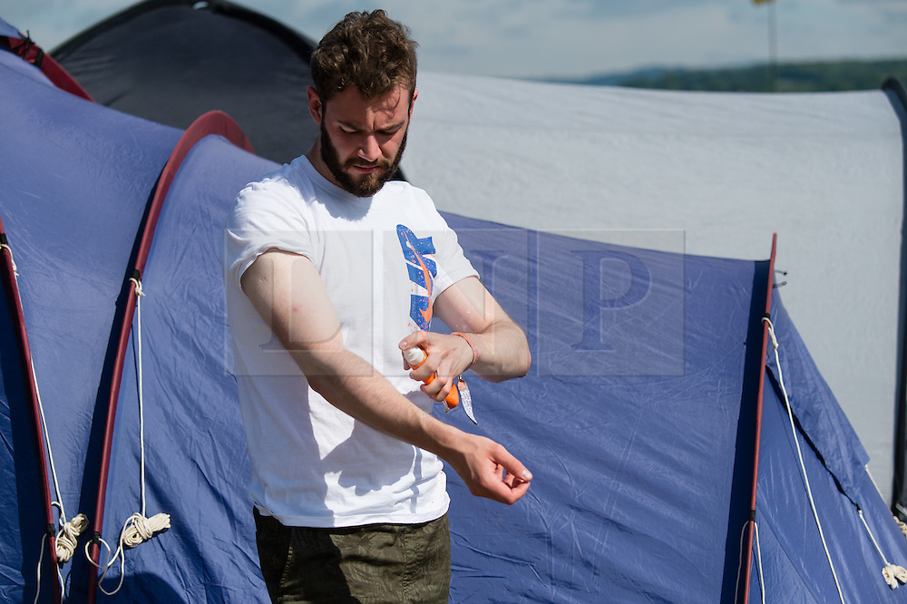 © Licensed to London News Pictures. 25/06/2015. Pilton, UK. Festival atmosphere at Glastonbury Festival 2015 on Thursday Day 2 of the festival.  A man applies sunscreen on a hot sunny morning.  This years headline acts include Kanye West, The Who and Florence and the Machine, the latter having been upgraded in the bill to replace original headline act Foo Fighters.   Photo credit: Richard Isaac/LNP