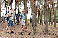 Full length of happy young couple trekking in forest