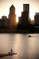 A cyclist sits on his bicycle with his child in back in a bike trailer on a dock over the Willamette river in Portland, Oregon.  Sunset while a passing motor boat.