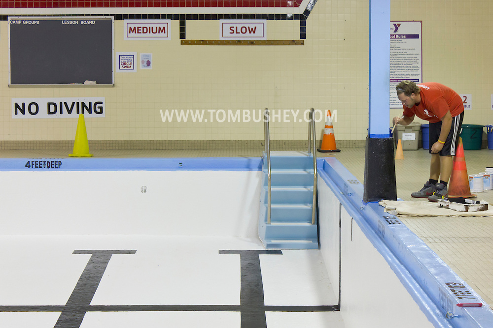 Middletown, New York - A workers paints a column by the empty pool at the Middletown YMCA on Tuesday, Aug. 28, 2012. The pool is briefly closed each year for maintenance.