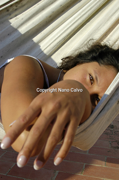 Close up of beautiful young female hand, with a french manicure, laying down in a hammock