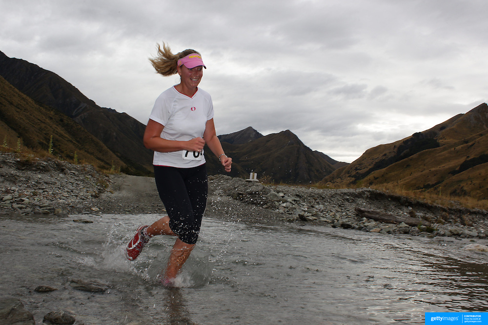 Runner Kay Caudwell crosses  Moke Creek on the Ben Lomond High Country Station during the Pure South Shotover Moonlight Mountain Marathon and trail runs. Moke Lake, Queenstown, New Zealand. 4th February 2012. Photo Tim Clayton