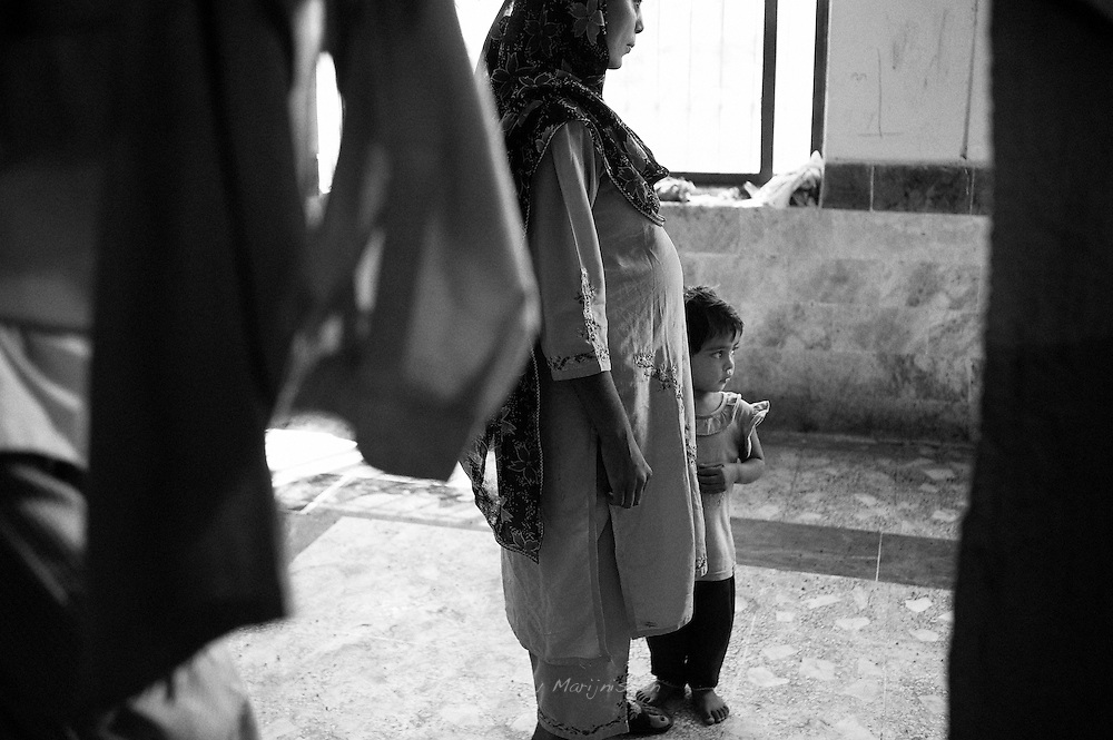 8 month pregnant Zaida and her 3 year old daughter have lived in Razadabad camp in Karachi for over 2 months and are waiting to return home. The flood destroyed their home and they wait for the money the government promised so they can start rebuilding their house. Karachi, Pakistan, 2010