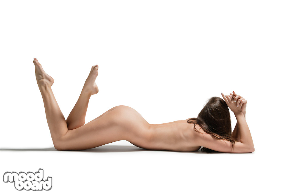 Sexy young naked woman lying on front with legs raised over white background