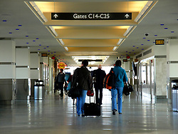 Travelers walking to their airline gate in an airport.