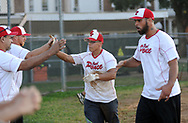 Real Ponce players Dave Sanchez (center) and Mark Capriotti (right) celebrate after Sanchez scored a run against Lajas during a semifinal playoff softball game in a league consisting of teams named after Puerto Rican cities Thursday, September 07, 2017 in Bristol, Pennsylvania. The teams in the league are named after various towns and areas in Puerto Rico, including Lajas, Real Ponce, Adjuntas and Comerio. (Photo by William Thomas Cain)