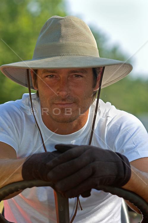 Portrait of a good looking  farmer leaning over steering wheel wearing hat and gloves