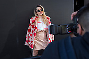 A model is photographed against a dark background on the street on the first day of London Fashion Week in the Strand, on 16th february 2018, in London, England,