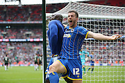 AFC Wimbledon striker Adebayo Akinfenwa (10) scores and celebrates with AFC Wimbledon defender Jon Meades (12) during the Sky Bet League 2 play off final match between AFC Wimbledon and Plymouth Argyle at Wembley Stadium, London, England on 30 May 2016.
