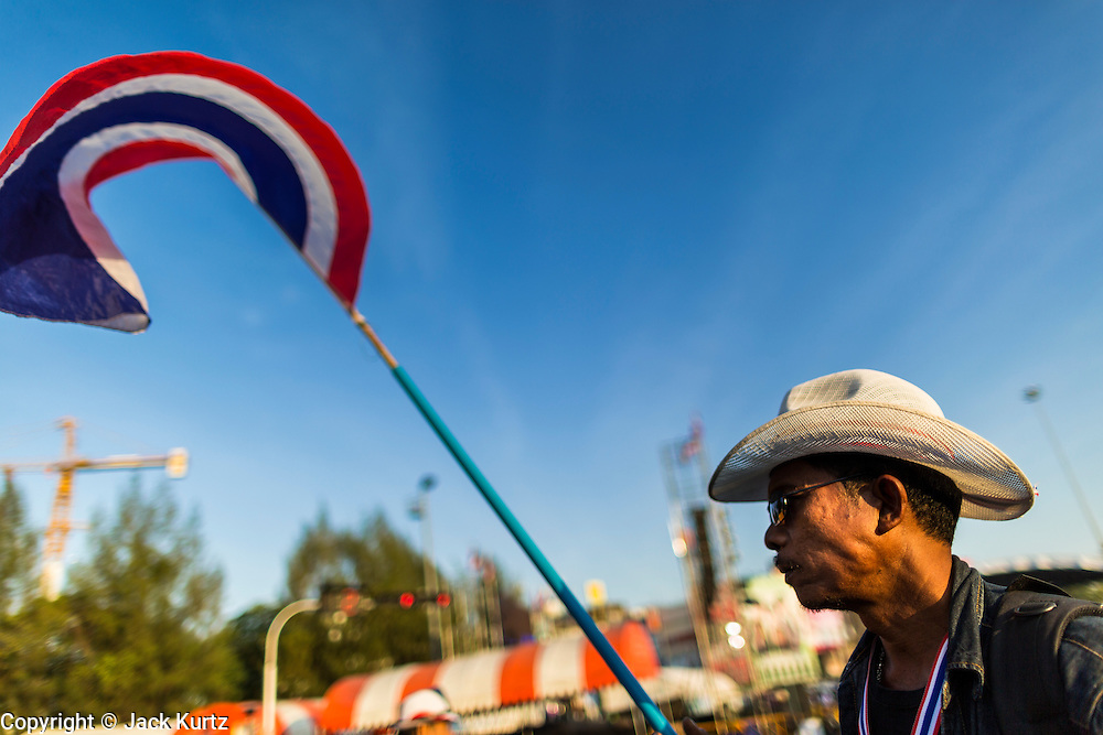 """14 JANUARY 2014 - BANGKOK, THAILAND: A Thai protestor carries a flag through the Victory Monument protest area. Tens of thousands of Thai anti-government protestors continued to block the streets of Bangkok Tuesday to shut down the Thai capitol. The protest, """"Shutdown Bangkok,"""" is expected to last at least a week. Shutdown Bangkok is organized by People's Democratic Reform Committee (PRDC). It's a continuation of protests that started in early November. There have been shootings almost every night at different protests sites around Bangkok, but so far Shutdown Bangkok has been peaceful. The malls in Bangkok are still open but many other businesses are closed and mass transit is swamped with both protestors and people who had to use mass transit because the roads were blocked.     PHOTO BY JACK KURTZ"""