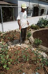 Gardener watering plants in garden in Havana; Cuba,