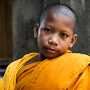A young monk sits for a portrait in the temples of Angkor Wat. Angkor Wat, Siem Reap, Cambodia