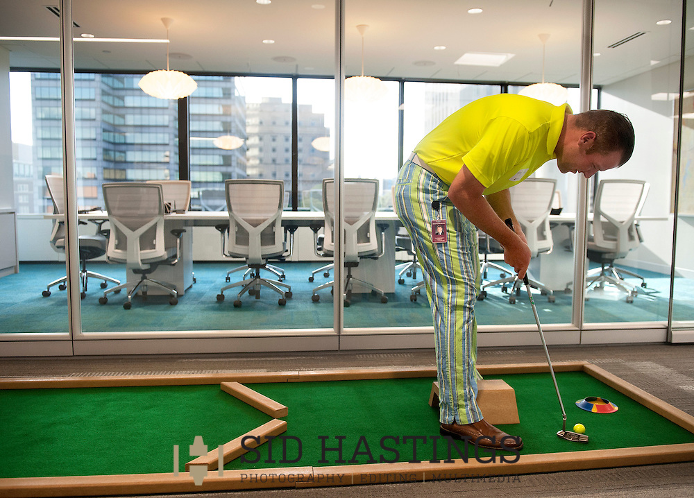 2 JUNE 2016 -- ST. LOUIS -- Steven R. Rommerskirchen of Anders CPAs + Advisors prepares to putt on the fifth hole of a putt-putt course laid out among the offices at the company in downtown St. Louis as part of Putt and Prosper 2016 Thursday, June 2, 2016. An after work happy hour sponsored by Anders' Young Professional Group for employees, customers and friends, Putt and Prosper scattered putt-putt holes throughout the firm's offices and raised funds for Stray Rescue of St. Louis. Photo © copyright 2016 Sid Hastings.
