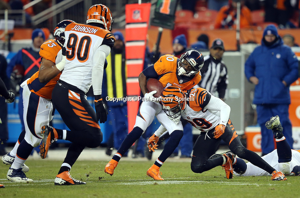 Denver Broncos wide receiver Emmanuel Sanders (10) grimaces as he gets hit hard by Cincinnati Bengals strong safety Leon Hall (29) as he catches a third quarter pass for a gain of 8 yards during the 2015 NFL week 16 regular season football game against the Cincinnati Bengals on Monday, Dec. 28, 2015 in Denver. The Broncos won the game in overtime 20-17. (©Paul Anthony Spinelli)