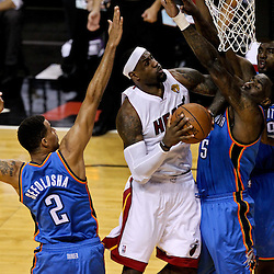 Jun 19, 2012; Miami, FL, USA; Miami Heat small forward LeBron James (6) shoots between Oklahoma City Thunder shooting guard Thabo Sefolosha (2) and center Kendrick Perkins (5) during the first quarter in game four in the 2012 NBA Finals at the American Airlines Arena. Mandatory Credit: Derick E. Hingle-US PRESSWIRE