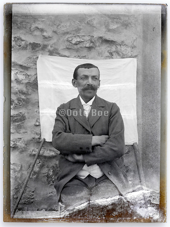 vintage deteriorating glass plate with portrait of man in daylight outdoor studio setting