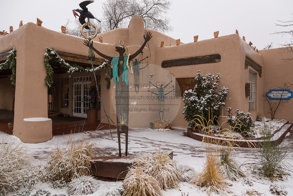Snow covers artwork in front of a gallery in the historic district December 12, 2015 in Santa Fe, New Mexico.
