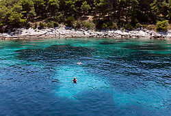 People swimming in an Adriatic cove on an unnamed island near Hvar. Natural color; not enhanced in Photoshop.