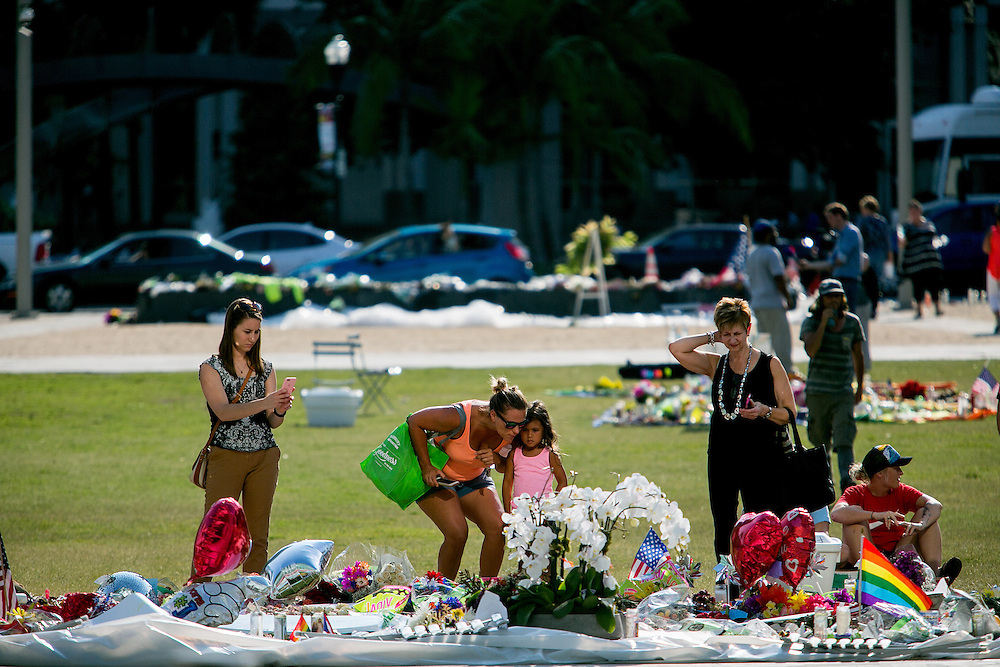ORLANDO - JUNE 15, 2016: Mourners gather at a memorial outside the Dr. Phillips Center for the Performing Arts to the 49 people killed in a shooting massacre in the Pulse nightclub in Orlando, Florida. CREDIT: Sam Hodgson for The New York Times.